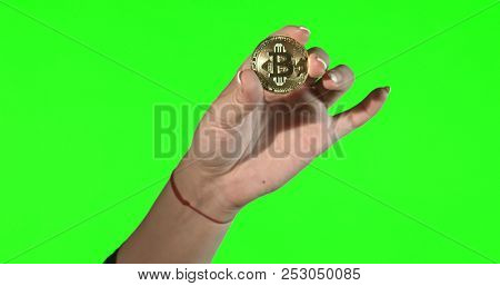 Hand holding crypto currency BTC Bitcoin coin on green screan background.