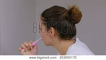 Healthy young woman brushing teeth in her bathroom.