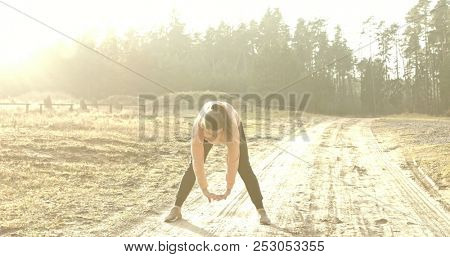 Woman working out doing stretching exercise in the park.