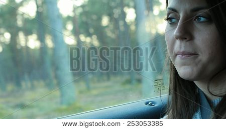 Young woman looking through a car window.