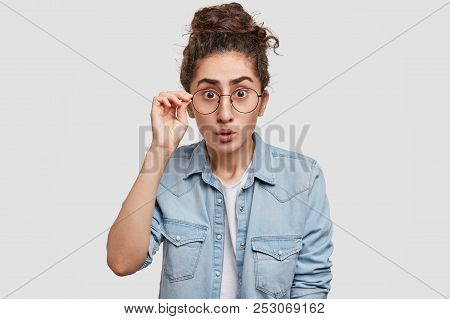 Photo Of Amazed Young Female Looks Surprisingly And Scrupulously At Camera, Can`t Understand Somethi