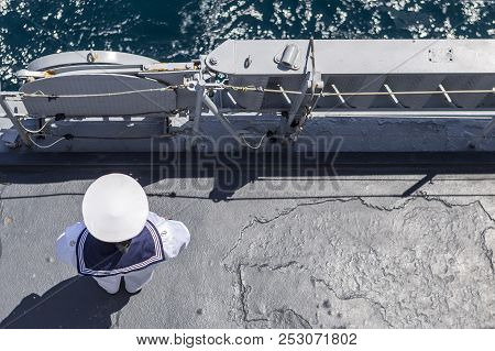 Sailor In White Uniform Standing Peacefully On The Deck Of A Warship. A Military Warship And Militar