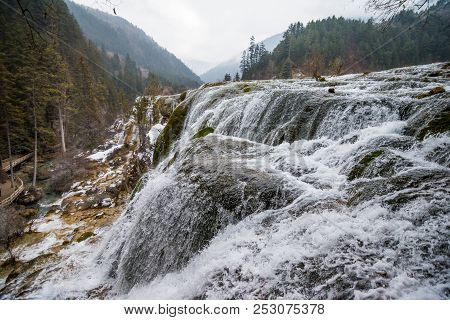 Waterfall In The Forest. Stream Of Water On The Rocks. Clean And Cold Water Over The Coniferous Fore