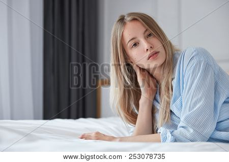 Horizontal Portrait Of Young Caucasian Female Rests On Bed In Room, Looks Natural And Healthy As Has
