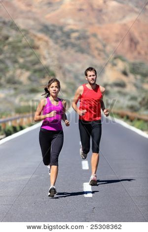 Couple running. Two runners training for marathon run outdoors on road in beautiful landscape. Man Caucasian runner and Asian woman runner.