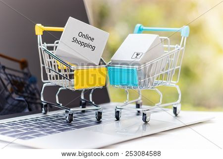 Cardboard Box In Shopping Cart On Laptop. Consumers Can Buy Products Directly From Seller Over Inter