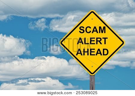 Scam Alert Caution Sign With A Blue Sky Background