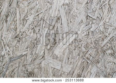 Old grey chipboard background top view. Aged osb panel texture or pressed and glued wood chips backdrop poster
