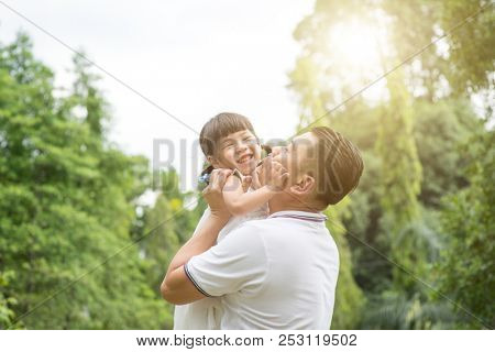 Asian family outdoors portrait. Father and daughter having fun at garden park.