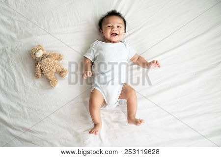Adorable Baby Boy In White Sunny Bedroom In Winter Morning. Newborn Child Relaxing In Bed. Family Mo