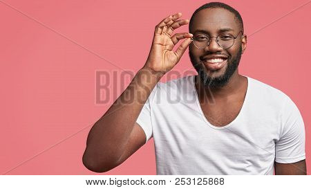 Cheerful African American Male With White Teeth, Has Broad Smile, Wears Casual T Shirt And Spectacle