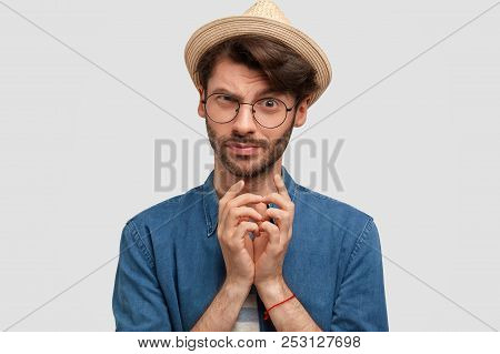 Attractive Bearded Male Keeps Hands Together And Looks With Intriguing Look, Raises Eyebrows, Has St