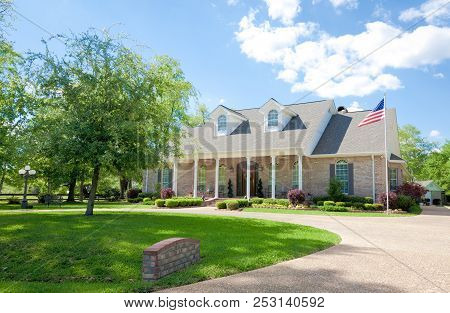 Large Ranch Style Coastal Home With A Front Porch. The Yard Features A Grass Lawn Trees. A Driveway