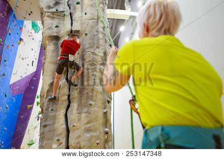 Photo from back of man climbing on wall and female trainer