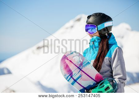 Photo of young woman tourist in helmet looking away with snowboard in hands against background of snow mountains
