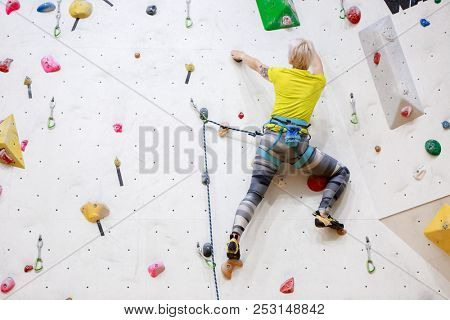 Photo from back of sports woman in yellow T-shirt scrambles on wall for climbing at workout