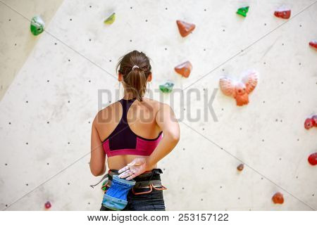 Photo from back of girl athlete with bag of talc against background of wall for rock climbing