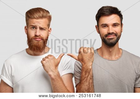 Handsome Ginger Male Frowns Face, Points With Thumb At His Male Companion, Express Different Emotion