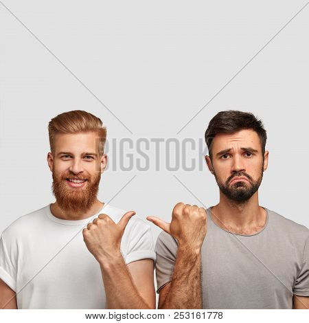 Happy Ginger Male Has Stubble Points With Thumb At His Brother Who Has Displeased Clueless Expressio