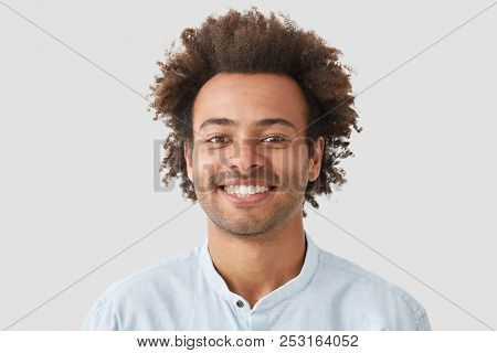 Mixed Race Curly Male With Broad Smile, Shows Perfect Teeth, Being Amused By Interesting Talk, Has B