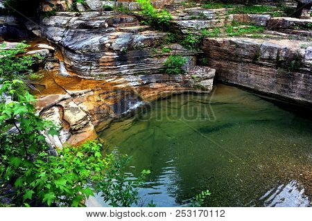 Water Cascades From A Ozark Mountain Spring.  Calm And Peaceful Pool Of Clear Water Sits Below Small