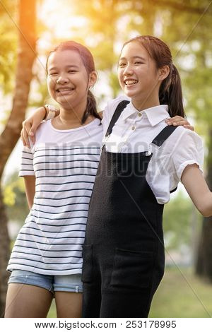 Cheerful Asian Teenager Relaxing With Happiness Emotion In Green Parkcheerful Asian Teenager Relaxin