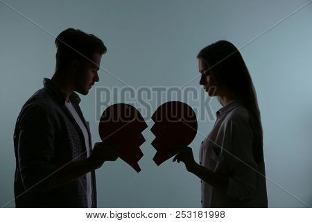 Silhouette Of Couple With Torn Paper Heart On Color Background. Relationship Problems