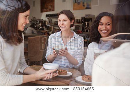 Female friends talking at a coffee shop, seen through window