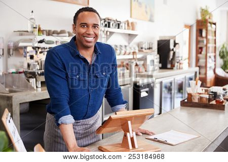 Young black male coffee shop owner leaning behind counter