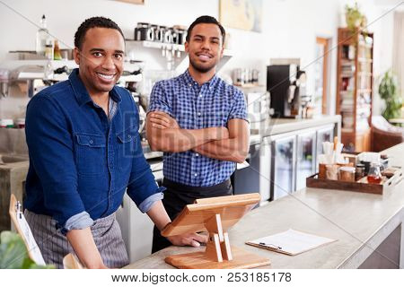 Two male owners behind the counter at their coffee shop