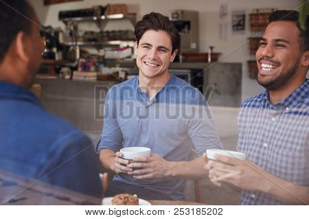 Three male friends laughing over coffee at a coffee shop