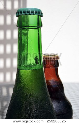 Close Up View Of Two Glass Bottle Of Beer Necks With Drops Against A High Key Background With Space