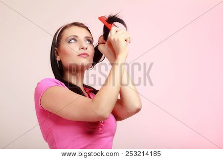 Portrait Of Childish Thoughtful Young Woman Combing Her Hair And Dreaming. Infantile Pensive Girl Wi