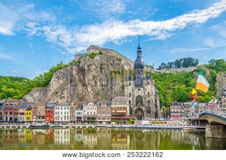 View At The Embankment Of Meuse River With Houses And Church Of Our Lady Assumption In Dinant, Belgi