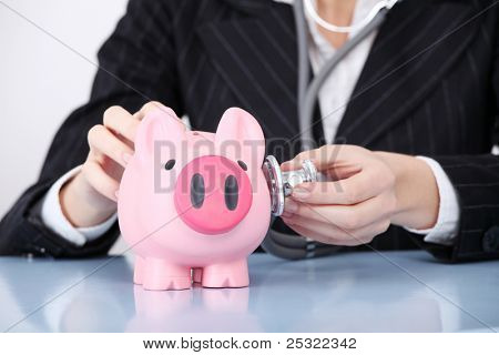 Closeup on examining pink piggy bank by caucasian businesswoman.