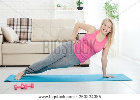 Working With Your Body. Full Length Of Beautiful Middle Aged Woman In Sportswear Doing Plank While S
