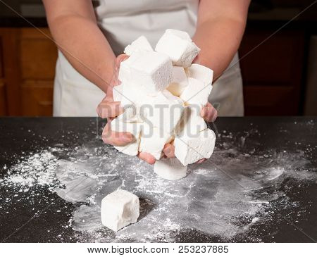One Marshmallow Falls From Large Handful Onto Slate Cutting Board