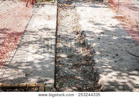 Sidewalk Construction Site For Repair Of The Asphalt Footpath Surrounded And Protected With Orange S