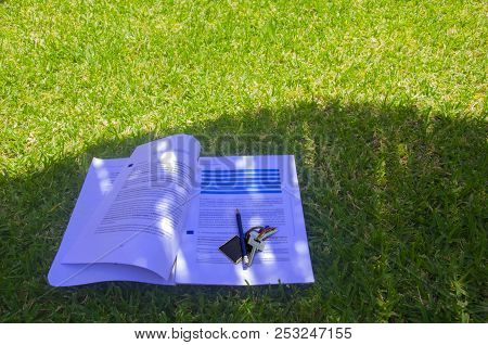 Papers With Lections To Study, Pencil And Keys In The Shadow On The Grass