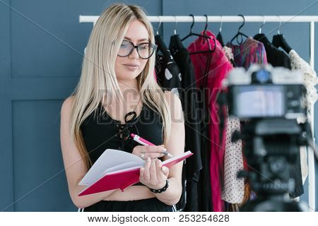 fashion stylist vlogging. social media influencer creating content. woman writing her ideas in a notepad. clothing showroom with stylish items on the rack. poster