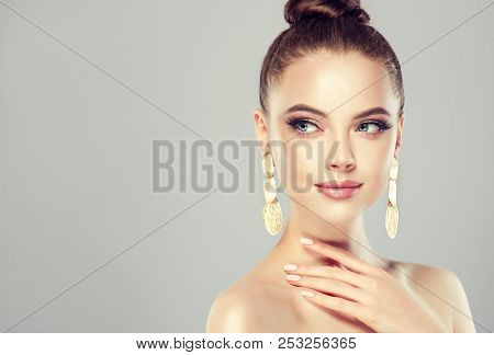 Beautiful Model Girl With Pink Manicure On Nails . Fashion Makeup And Cosmetics . Big Golden Shine
