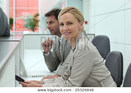Man and woman working behind a reception desk