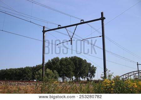 Railroad Track At Moordrecht Heading To Rotterdam In The Netherlands With Electricity Wires With Pol