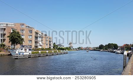 River Vliet In Leidschendam With Blue Sky And Windmill Salamander On The Background In The Netherlan