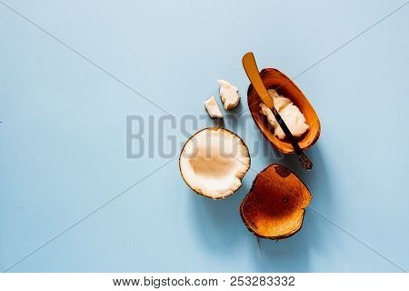 Organic Healthy Coconut Butter And Fresh Coconut Fruit On Pastel Blue Background Flat Lay. Natural O
