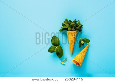 Sweet Waffle Cone With Fresh Leaves Mint On Pastel Light Blue Background Flat-lay. Spring Or Summer
