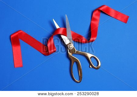 Ribbon And Scissors On Color Background, Top View. Ceremonial Red Tape Cutting