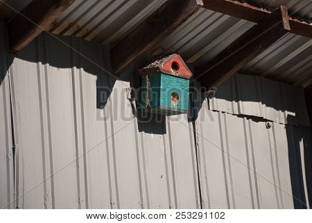 Sunlit Birdfeeder On The Side Of A Barn