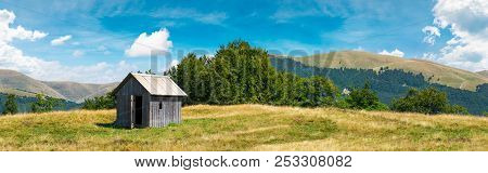 Wooden Hut On A Grassy Meadow. Forested Mountains In The Distant. Beautiful Panorama Of Summer Count