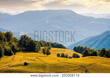Hut On The Grassy Hill At Sunset. Beautiful Mountain Ridge In The Distance. Wonderful Summer Landsca